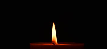 Red burning candle. With flame on black background Royalty Free Stock Photos