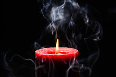 Red burning candle. With flame and smoke on black background Royalty Free Stock Photos