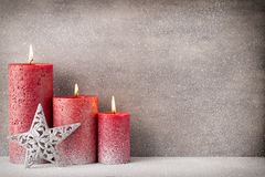Red burning candle on a snow background. Interior items. Stock Image