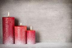 Red burning candle on a snow background. Interior items. Stock Images