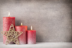 Red burning candle on a snow background. Interior items. Stock Photos