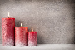 Red burning candle on a snow background. Interior items. Royalty Free Stock Photo