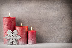Red burning candle on a snow background. Interior items. Royalty Free Stock Images
