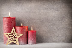 Red burning candle on a snow background. Interior items. Stock Photo