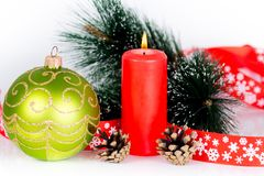 Red burning candle and xmas tree decorations. Christmas composition isolated on white Royalty Free Stock Image