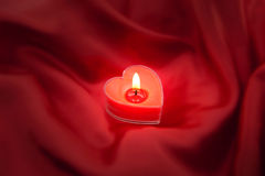 Red burning heart shaped candle on satin background Royalty Free Stock Photography