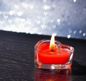 Red burning heart shaped candle on silver hearts bokeh Royalty Free Stock Images