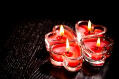 Red burning heart shaped candles on black wood table Stock Photos