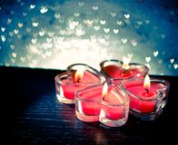 Red burning heart shaped candles on blue hearts bokeh Royalty Free Stock Photography