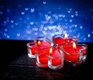 Red burning heart shaped candles on blue hearts bokeh Royalty Free Stock Images