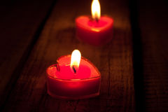 Red burning heart shaped candles on rustic wooden table. Valenti Royalty Free Stock Photo