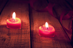 Red burning heart shaped candles on rustic wooden table. Valenti. Ne's Day and Mother's Day background. Toned image. Soft focus stock photography