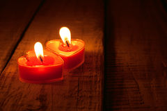 Red burning heart shaped candles on rustic wooden table. Valenti Stock Images