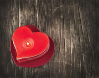 Red burning heart shaped candles on wooden background. Royalty Free Stock Images