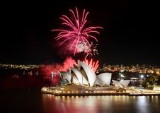 Red bursts of fireworks streaming up from the Sydney Opera House at night. Sydney, Australia - March 8, 2018: An impressive fireworks show hosted by the Sydney royalty free stock photos