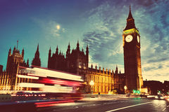 Red bus, Big Ben and Westminster Palace in London, the UK. at night. Moon shining. Vintage. Red bus in motion, Big Ben and Westminster Palace in London, the UK Royalty Free Stock Photos