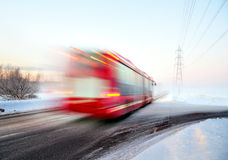 Red bus in blurred motion in winter. Red bus in blurred motion on cold foggy winter day in rural area Stock Photo
