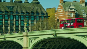 Red Bus crossing the Westminster Bridge. On a sunny day stock video