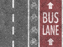 Red bus lane on asphalt Royalty Free Stock Image