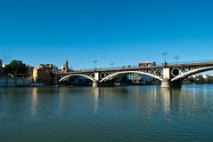 The red bus passes over the Triana bridge over the Guadalquivir river in Seville royalty free stock photography