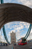 Red bus passing through the Tower Bridge in London. Stock Photos