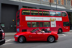 Red bus and red car in London. Red sport car next to a London's red bus Stock Images