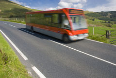 Red bus on rural road. In Wales Stock Photos
