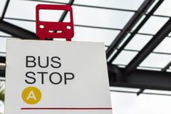 Red bus shape on bus stop sign Stock Photography