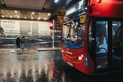 Red bus waiting on red light by pedestrian crossing in Canary Wharf, London, UK. London, UK - January 26, 2019:Red bus waiting on red light by pedestrian royalty free stock photo