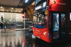 Red bus waiting on red light by pedestrian crossing in Canary Wharf, London, UK. London, UK - January 26, 2019:Red bus waiting on red light by pedestrian stock images