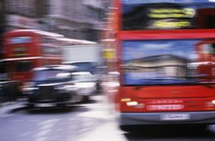 Red buses and black cabs on road in London motion blur Royalty Free Stock Images