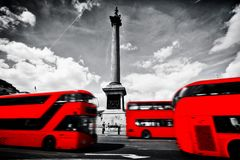 Red buses in motion on Trafalgar Square in London, UK. Nelson's column Royalty Free Stock Image