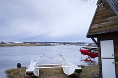 Red bush plane parked on frozen lake with skis on. Stock Photo
