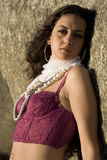 Red bustier by rocks. A young brazilian brunette wearing a dark red bustier by some rocks royalty free stock photos