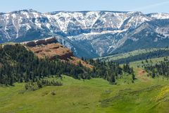 Red butte snowcapped mountains meadow. The red butte hillside hill and high snowcap mountain forest green grassy slopes meadows valley western wilderness scene Stock Image