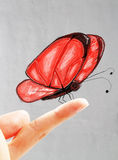 Red butterfly on finger Stock Photos