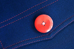 Red button on blue textile Stock Photography