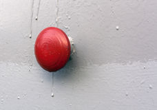 Red button on gray metal wall. Royalty Free Stock Image