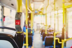 Red button STOP on the bus. Bus with yellow handrails and blue seats. Photo with the sun effect, glare on the lens from the light. Spacious interior of the bus royalty free stock images