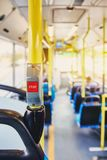 Red button STOP on the bus. Bus with yellow handrails and blue seats. Photo with the sun effect, glare on the lens from the light. Spacious interior of the bus royalty free stock photos