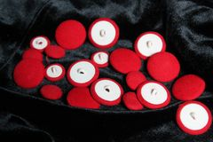 Red buttons. Red soft buttons lay on  black velvet prepare for sew in jacket royalty free stock images