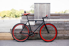 Red bycicle parked near bench in park Royalty Free Stock Images