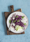 Red cabbage and apple slaw. Tasty vegetarian diet food. On a blue background Stock Photography