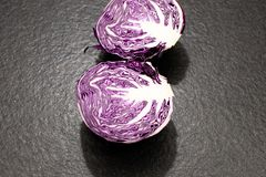 red cabbage ball cut in half with all the leaves on a black gran stock photography