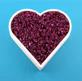 Red cabbage in a heart. Raw chopped red cabbage salad in a heart, isolated against a blue background royalty free stock image