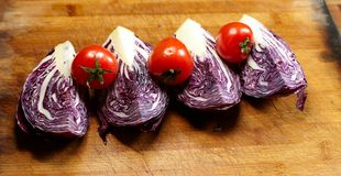 Red cabbage slices and red cherry tomatoes Royalty Free Stock Images