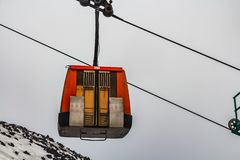 A red cabin of the cable cars with closed door under the black vulcan mountain Etna with white snow on the gray sky background in royalty free stock photos