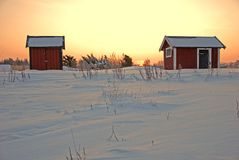 Red cabins in sunrise. And patterns in the snow Royalty Free Stock Image