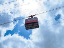 Red cable car against the cloudy blue sky red cable car on the mountain royalty free stock photos