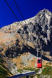 Red cable car arrives at Skalnate pleso from Lomnicky peak Stock Image